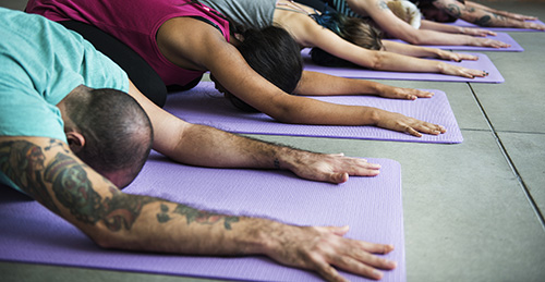 Group of diverse people are joining a yoga class with 7daysPresent AirBnB Experience host, deyani.